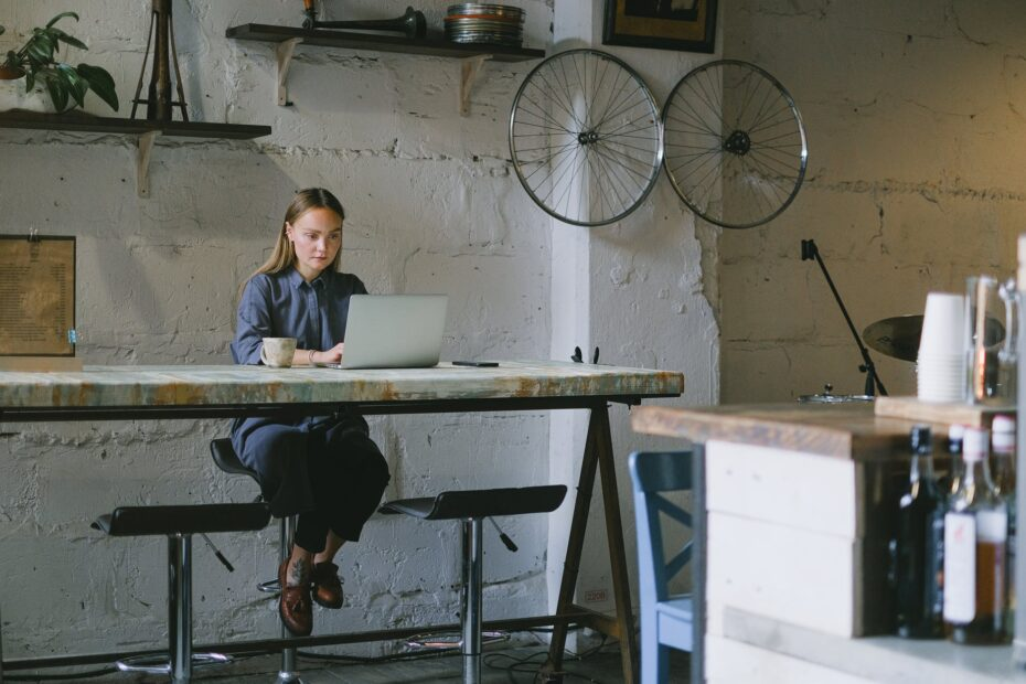 woman working remotely on laptop with coffee cup in loft